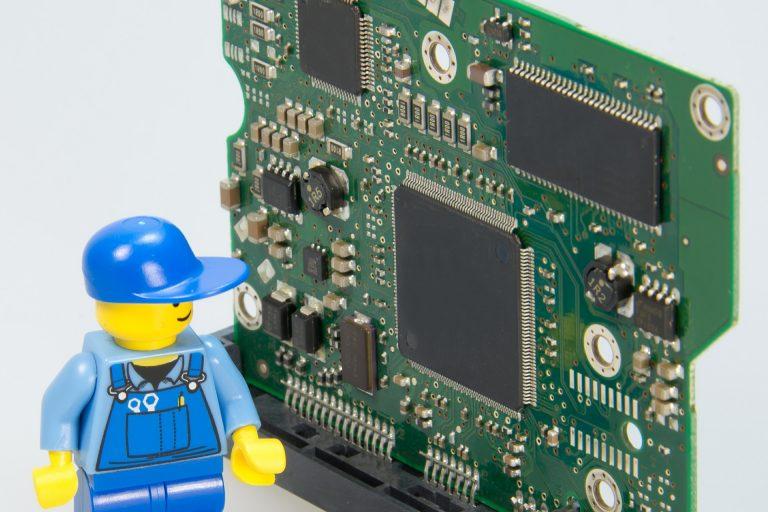 Imagem de bonequinho de Lego observando um componente de computador