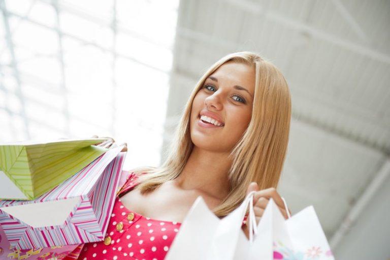 Mulher segurando sacolas de lojas.