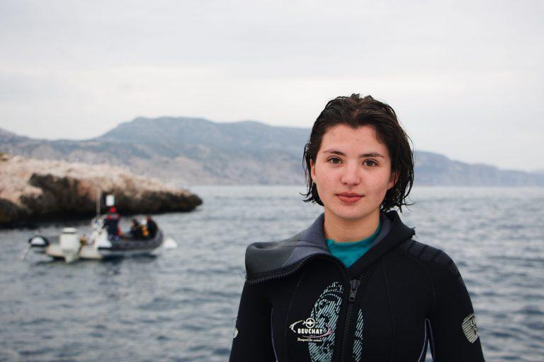 Imagem mostra uma mergulhadora posando para foto, com o mar e uma cordilheira ao fundo. Ela está com a roupa de mergulho aberta na região do pescoço, revelando a gola uma segunda roupa.