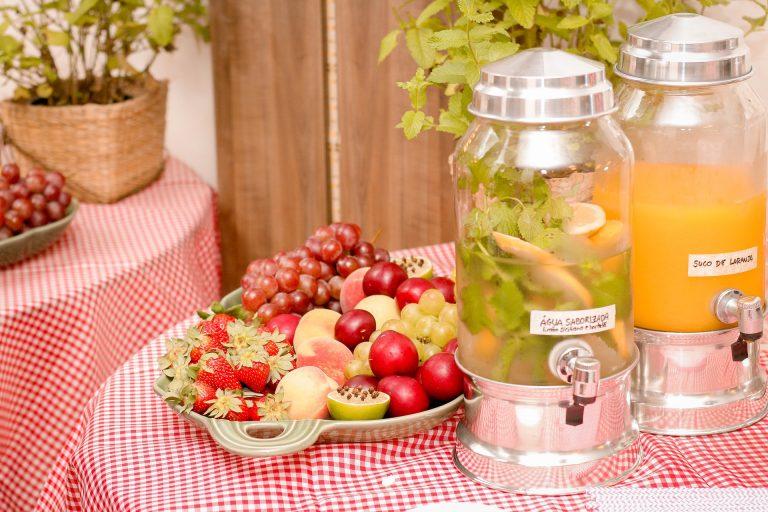 Imagem de duas suqueiras de vidro com e metal sobre mesa com frutas