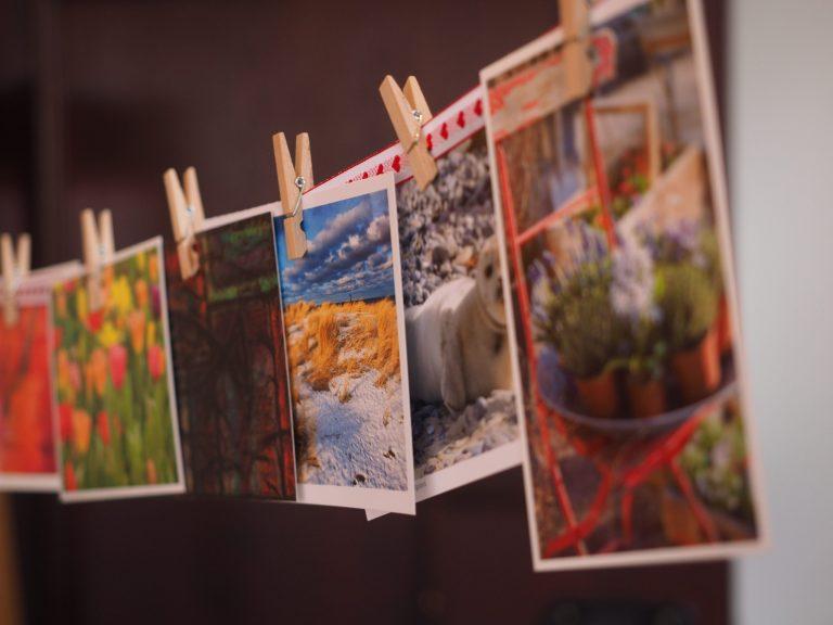 Na foto um varal de fotos com prendedores de madeira e diversas fotografias diferentes.