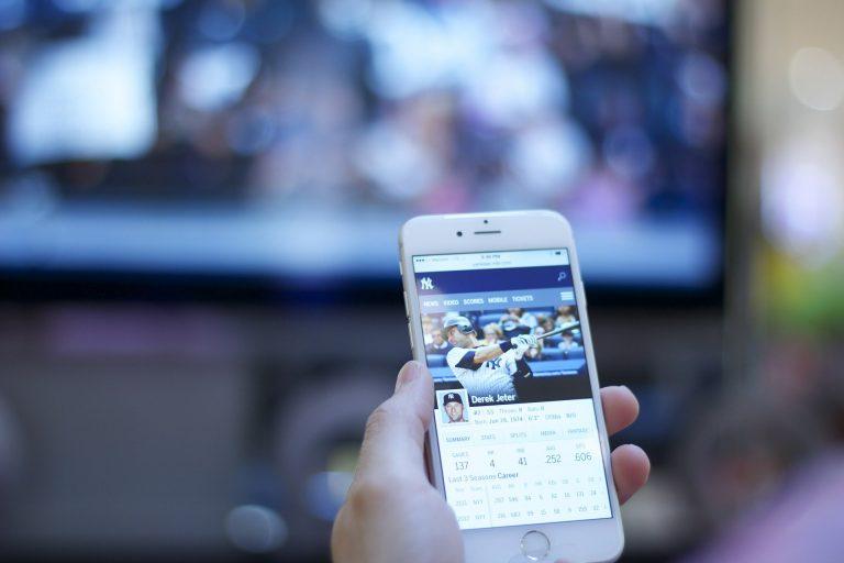 Imagem com uma pessoa assistindo um vídeo no celular de frente para uma televisão ligada