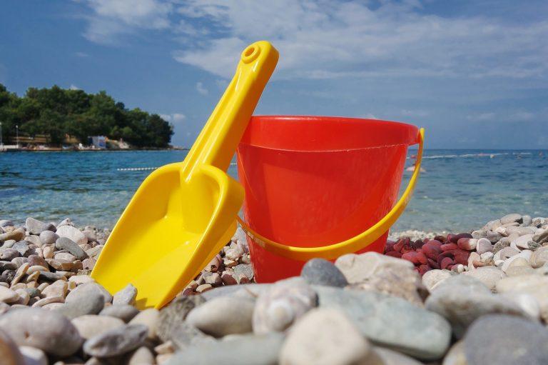 Imagem de baldinho e pazinha de plástico na beira da praia