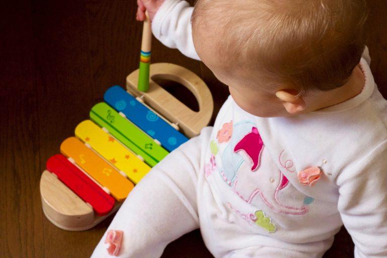 Na foto uma bebê com um brinquedo de madeira.