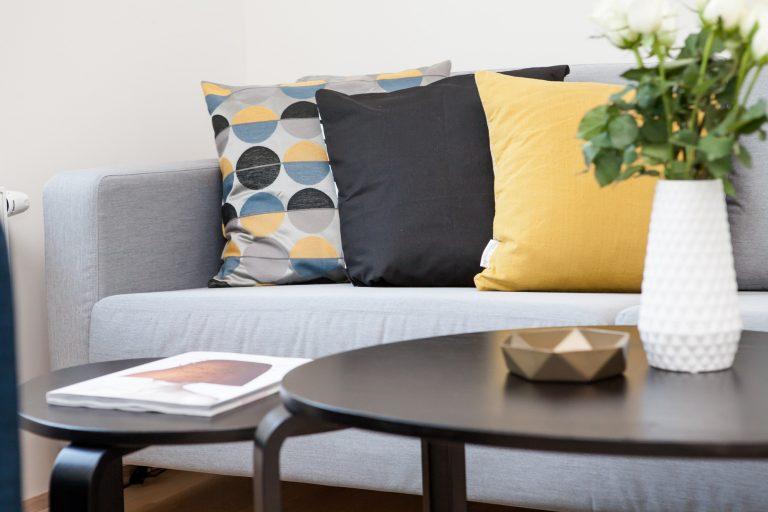 Imagem de um sofá com várias almofadas.
