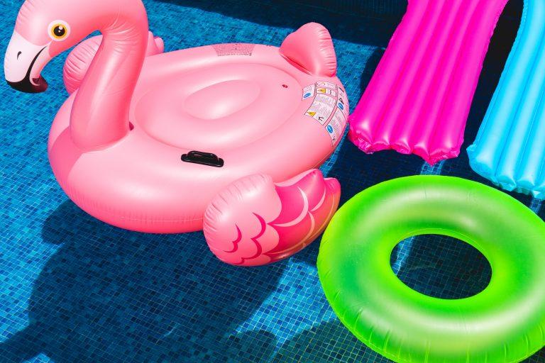 Imagem mostra bóias de formatos diversos boiando sob a água de uma piscina, num dia de sol..