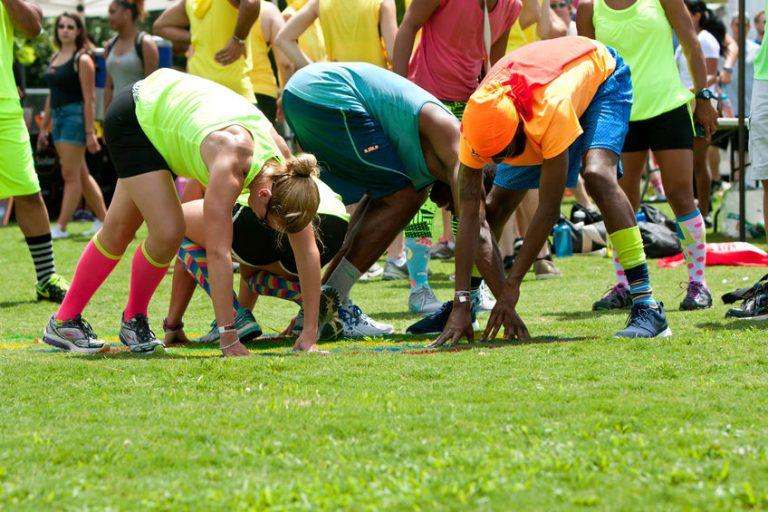Imagem mostra um grupo jogando twister sobre a grama, com muitas pessoas ao redor.