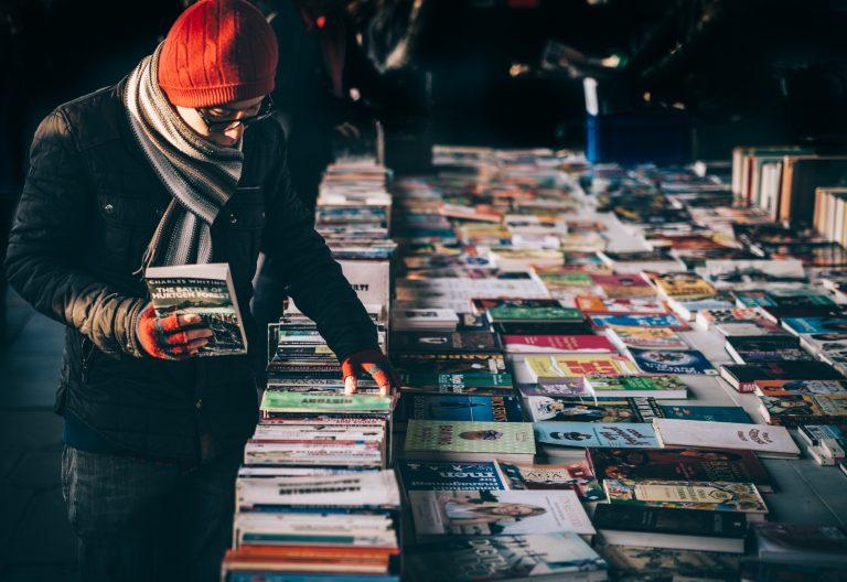 Imagem mostra um homem, bem agasalhado, escolhendo livros dispostos numa mesa larga, que ocupa todo o quadro da foto. Ele segura um livro em sua mão direita.