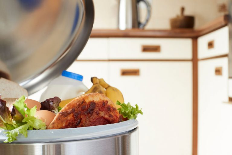 Imagem de lixeira de cozinha cheia de lixo e com a tampa aberta