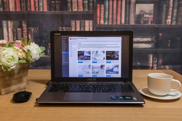 Notebook em mesa com xícara ao lado.