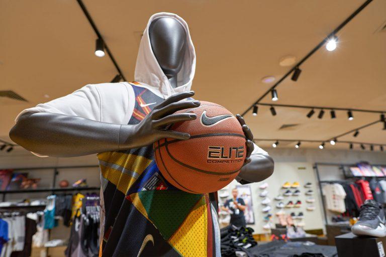 Imagem mostra um manequim de uma loja da Nike segurando uma bola de basquete da marca, da linha Elite.