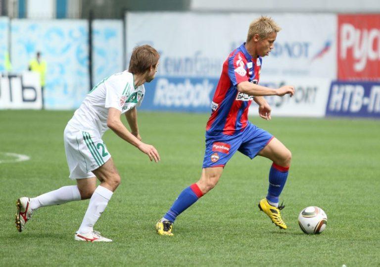Imagem mostra o jogador japonês Honda durante uma partida do CSKA Moscou. Ele tem a bola sob seu domínio, e usa chuteiras Mizuno.