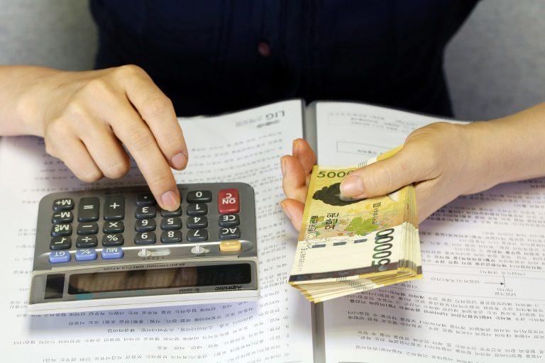Mulher usando calculadora, com notas de dinheiro na outra mão.