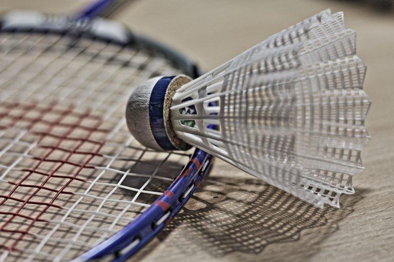 Imagem mostra, em plano detalhe, uma peteca repousando, com seu peso para baixo, sobre a rede de uma raquete de badminton.