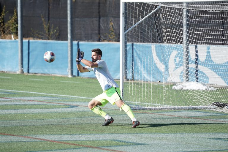 Imagem mostra um goleiro saltando para a sua direita, com as mãos na altura do rosto, prestes a defender uma bola.