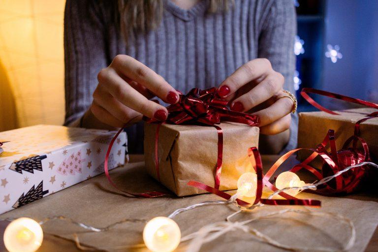 Na foto uma mulher embrulhando presentes.
