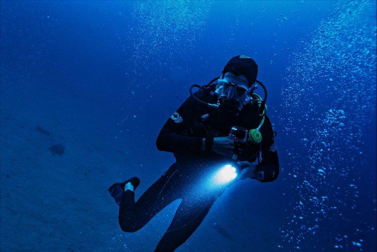Imagem mostra um mergulhador debaixo d'água. Eles está com roupa e equipamento completo, e segura uma lanterna com uma câmera acoplada.