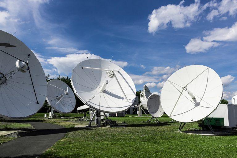 Imagem com várias antenas parabólicas brancas apoiadas em um chão com grama