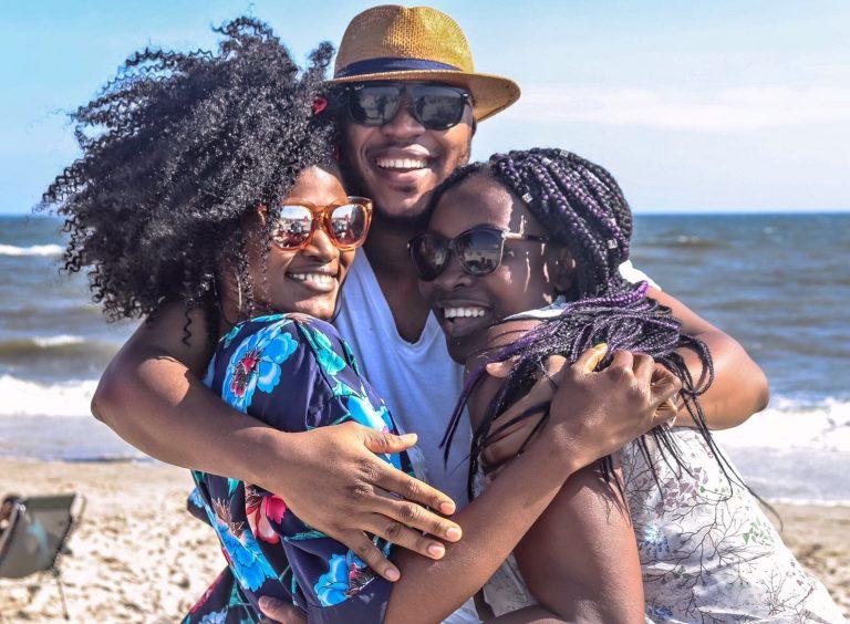 Na foto um homem e duas mulheres se abraçando sorrindo em uma praia.