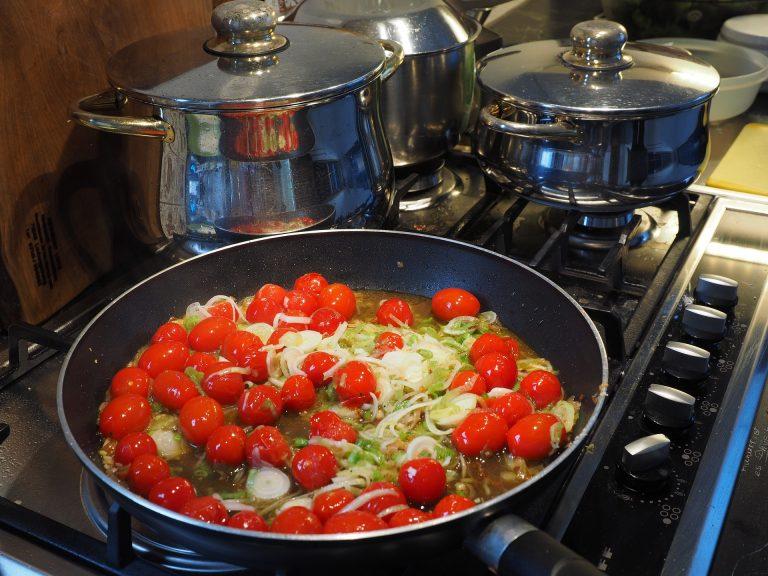 Imagem de fogão a gás com panela contanto tomates e vegetais