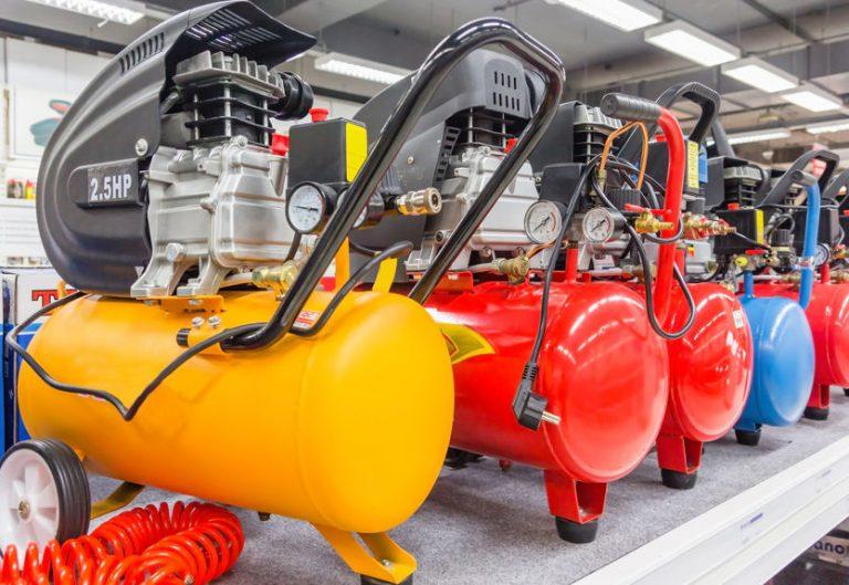 Imagem mostra uma fileira de compressores, com tanques coloridos, ao fundo, as luzes e superfícies de um ambiente industrial.