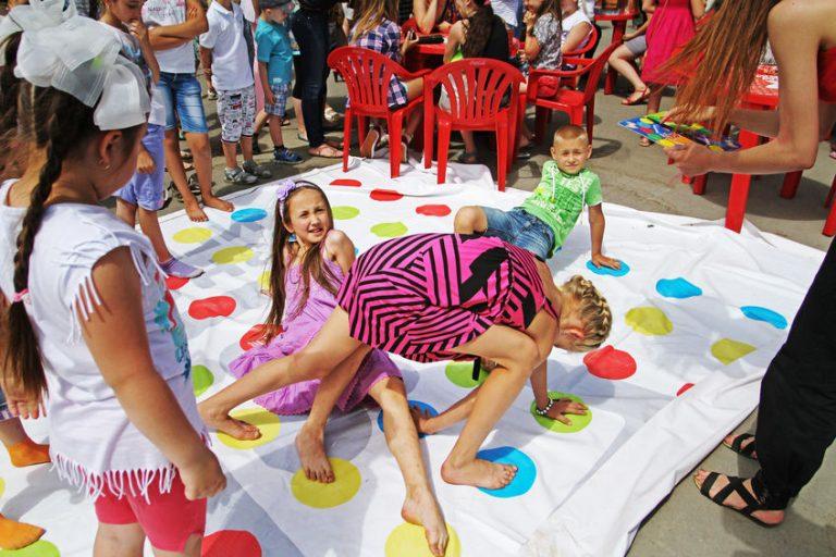 Imagem mostra crianças brincando de twister num grande tapete de bolinhas.