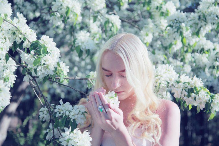 Imagem de uma mulher cheirando flores.