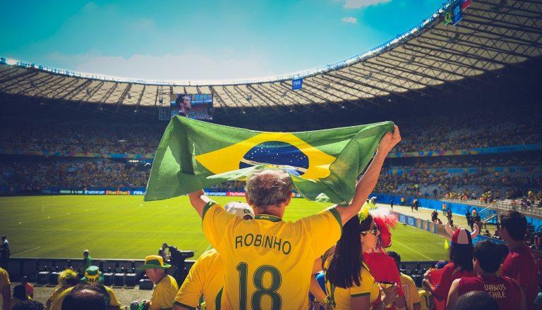 Na foto um homem de camiseta do Brasil segurando uma bandeira dentro de um estádio de futebol.