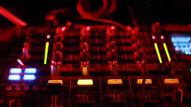 Imagem mostra uma mesa de som ligada, com botões e visores iluminados, sob uma intensa luz vermelha.