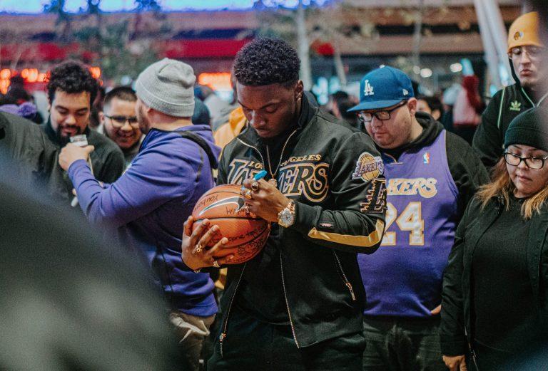 Imagem mostra um homem em meio a uma multidão assinando uma bola de basquete da Nike, que já tem diversas outras assinaturas.