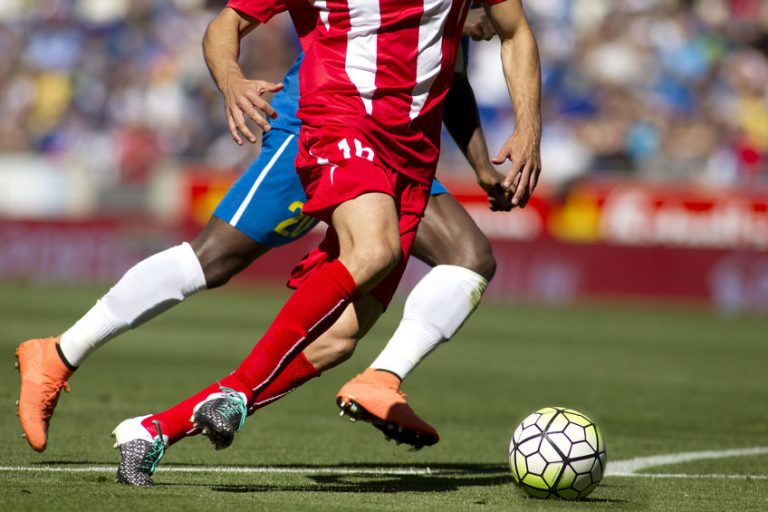 Imagem mostra as pernas de dois jogadores adversários durante um jogo de futebol.