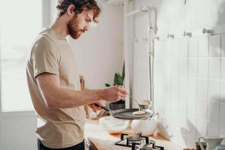 Imagem de um rapaz preparando panquecas.