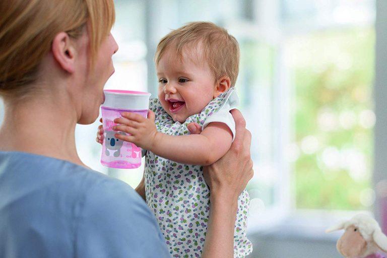 Imagem de um bebê segurando um copo infantil.
