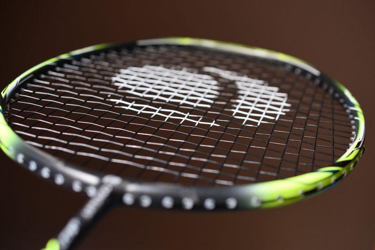 Imagem mostra um close de uma raquete de badminton, com o foco seletivo no meio de sua rede.