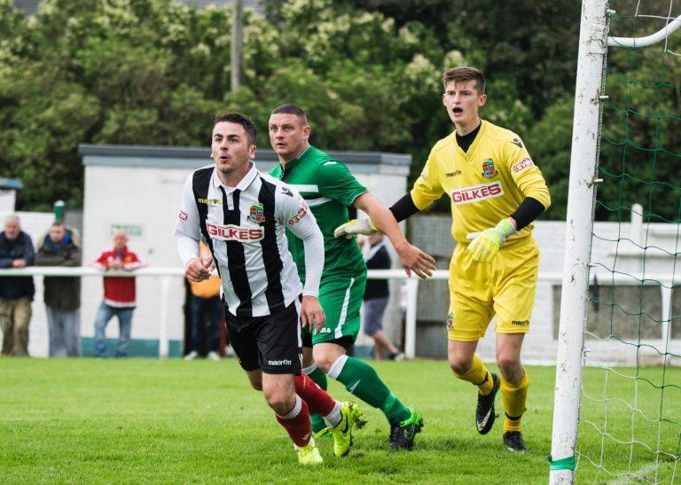 Imagem mostra o momento de um jogo de futebol em que dois adversários e o goleiro dividem espaço dentro da pequena área, enquanto olham para fora do quadro.