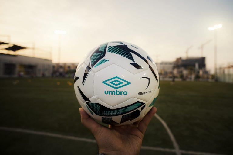 Imagem mostra uma mão segurando uma pequena bola da Umbro, com um campo de treinamento ao fundo, desfocado.