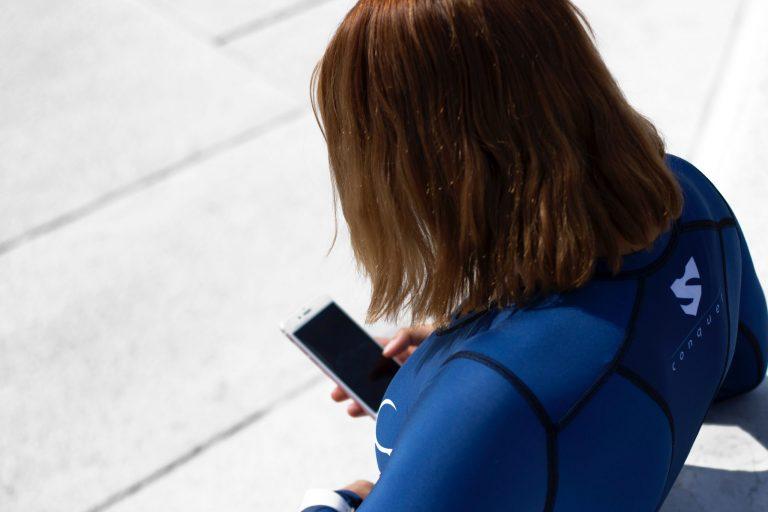 Imagem mostra uma mergulhadora fora d'água. Ela está de costas para a câmera, usando uma roupa de mergulho e mexendo no seu celular.
