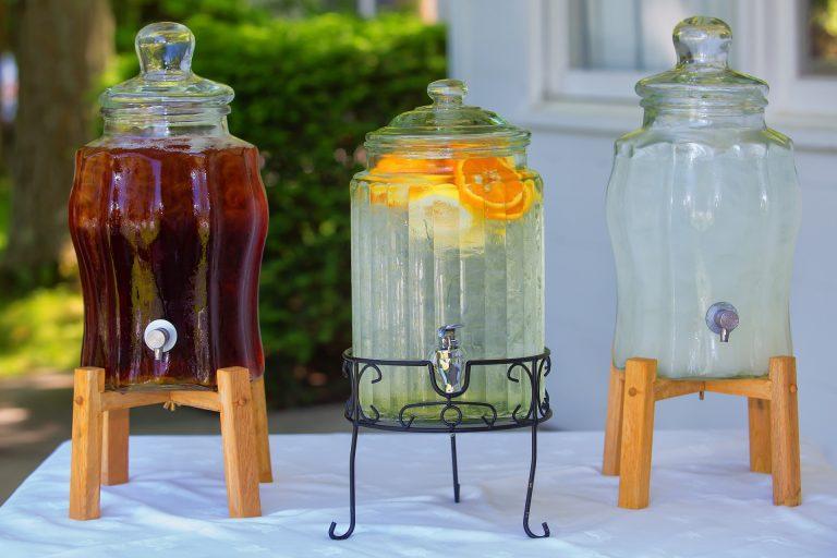 Imagem de três suqueiras de vidro com suportes de madeira e metal