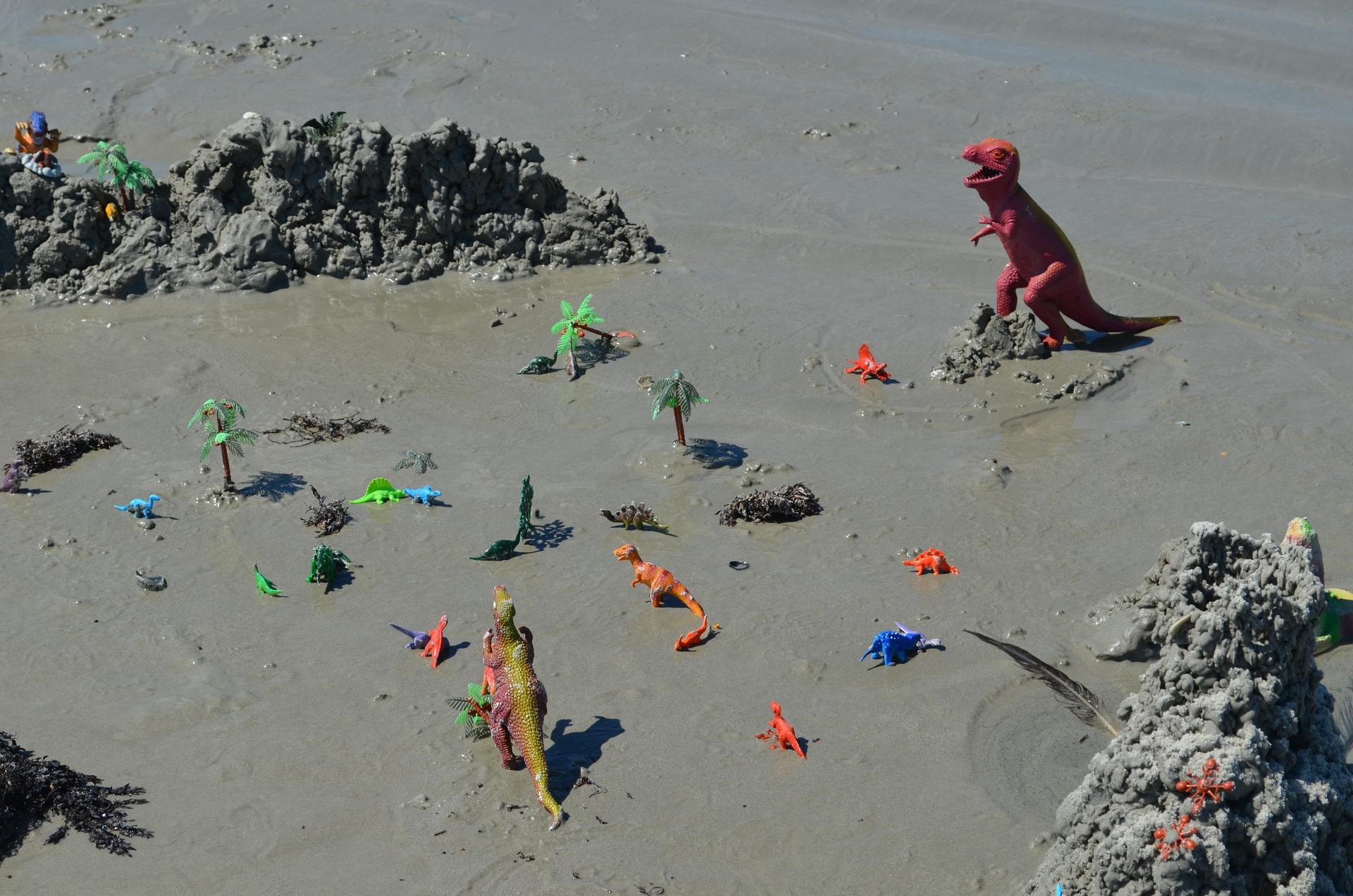 Imagem de dinossauros de brinquedo na areia da praia
