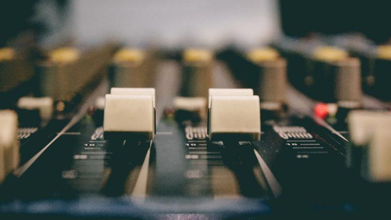 Imagem mostra, em foco seletivo, dois controladores de nível de uma mesa de som antiga.