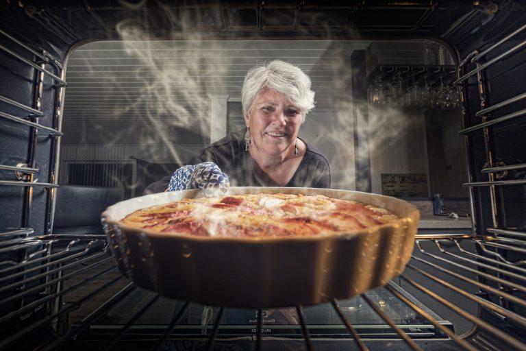 Imagem de mulher tirando uma torta de um forno elétrico Electrolux
