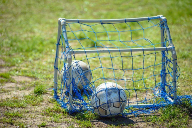 Imagem mostra duas bolas dentro de um mini gol, todos sobre um campo esburacada e com parcos tufos de grama.