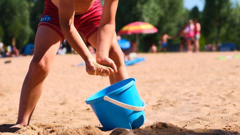Imagem de criança colocando areia de praia dentro de um baldinho de plástico