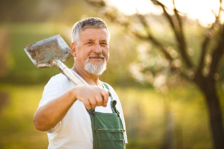 senhor sorrindo trabalhando de macacão com pá pendurada no ombro