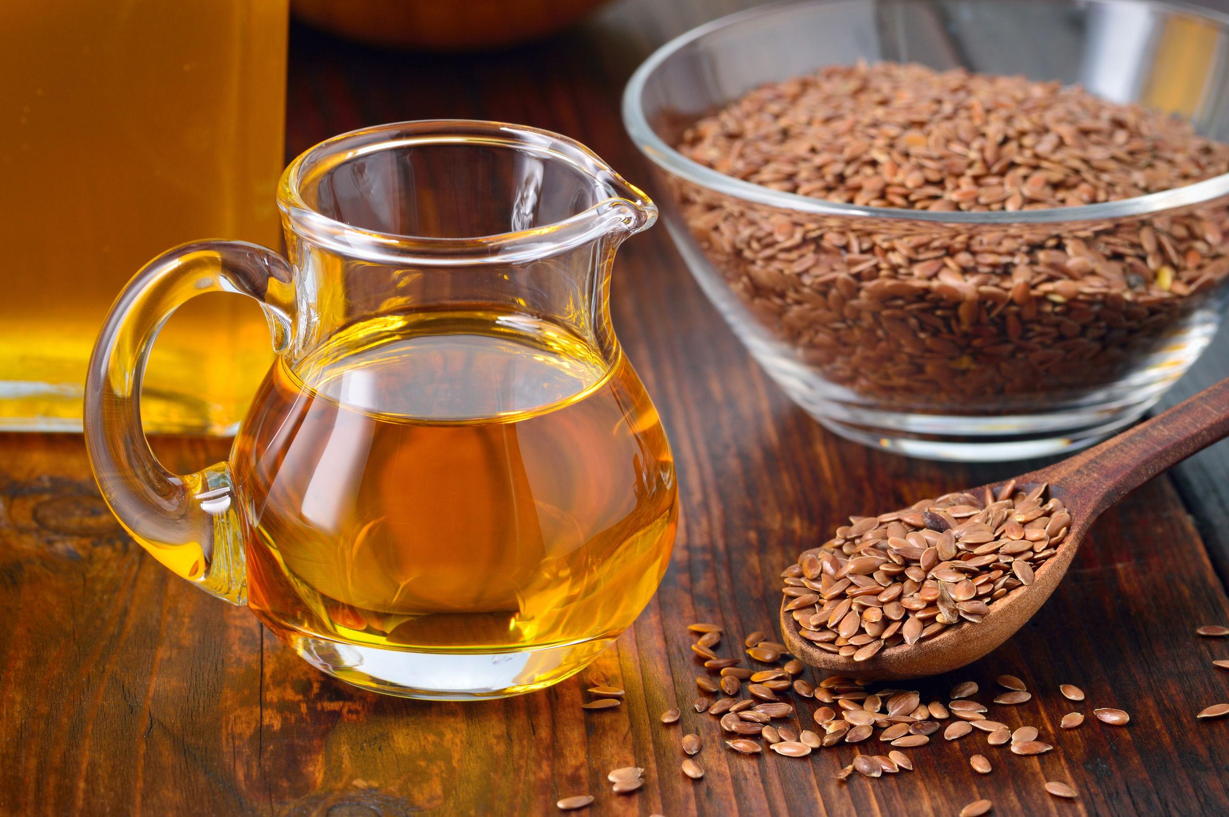 Foto de uma jarra de vidro pequena com óleo de linhaça, ao lado de unha vasilha e de uma colher de pau, ambas com semente de linhaça. Todos os objetos estão em cima de uma superfície de madeira.