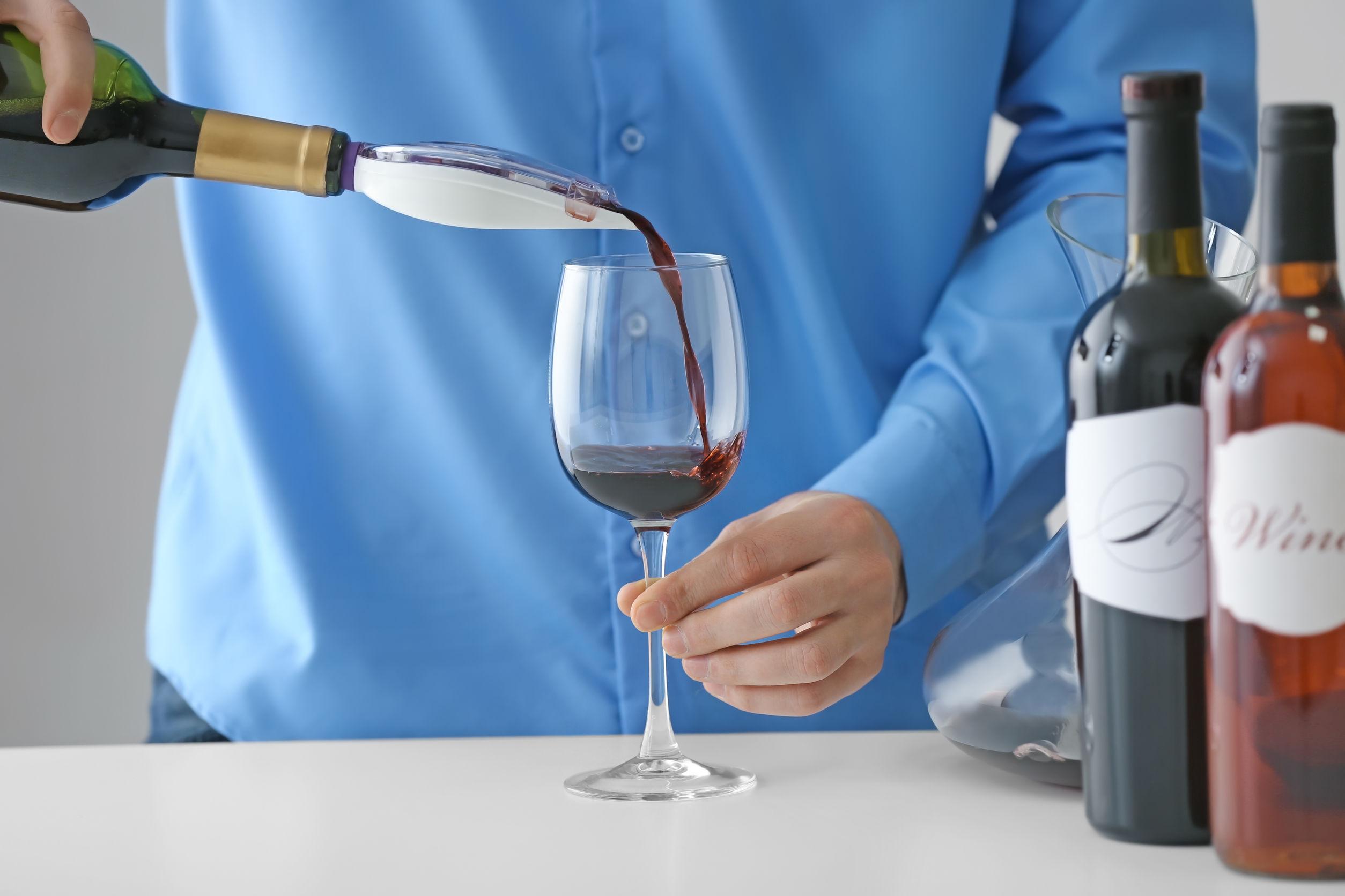 Imagem de pessoa usando um aerador acoplado na garrafa para servir vinho tinto