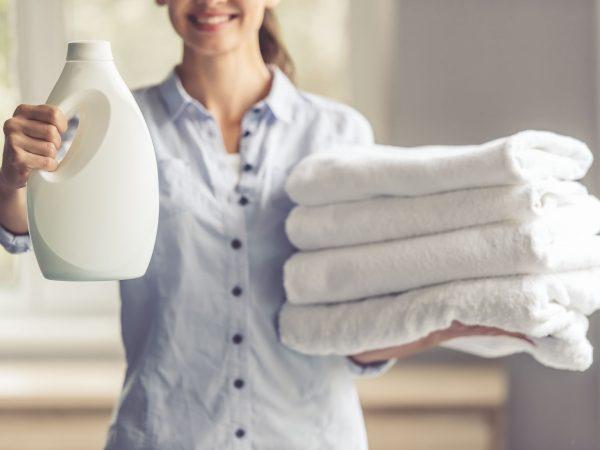 Imagem de mulher segurando uma embalagem de amaciante e toalhas brancas
