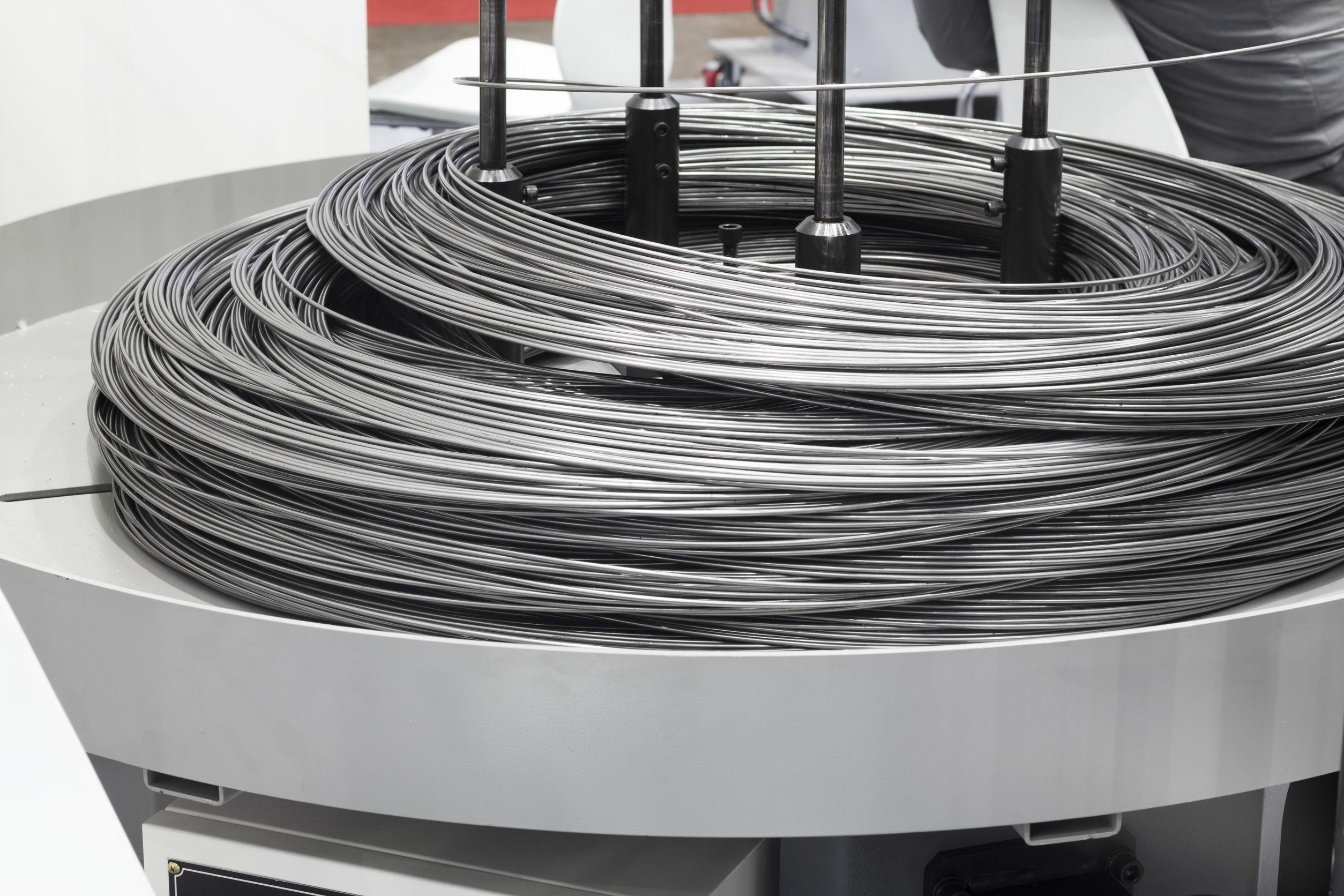 Imagem de rolo de arame galvanizado sendo utilizado em máquina industrial