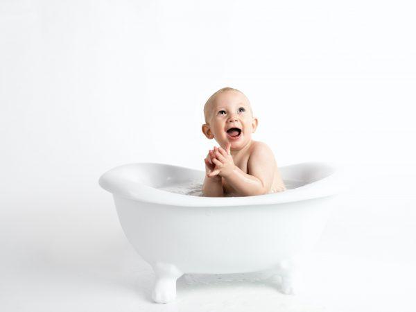 Foto de um bebê alegre, com a boca aberta, dentro de uma banheira branca, com água, em um fundo branco.