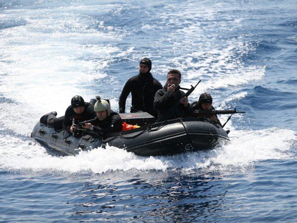 6 militares trajados de preto, armados com rifles em cima de um bote inflável negro em alto mar.